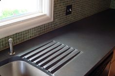 Charcoal concrete countertop with integrated drainboard.