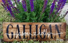 Wood sign personalized with painted last name and vinyl first names of couple with heart.