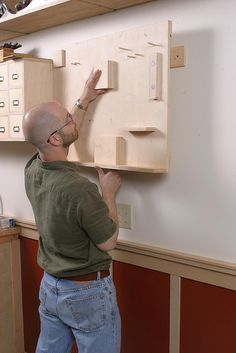 Smart Garage Workshop by Matthew Teague All toolboards and wall cabinets are hung on French cleats, making them easy to re-arrange. Hangers are screwed to the wall studs, which are aligned with the stiles in the wainscoting.