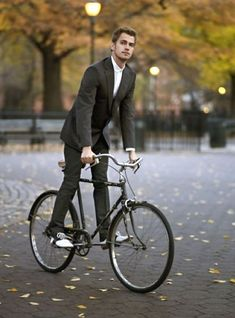 Suited Man. On A Bike.