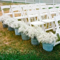 Galvanized buckets filled with babys breath lining the ceremony aisle.
