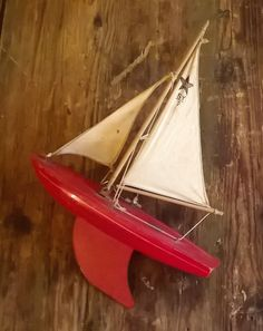 A charming vintage Star sailboat toy or pond yacht. Nice original condition - red-painted hull and keel with Star Yacht decal on deck. All original sails and yards. Hinged mast to collapse down. Solid wood boat hull with metal keel. Some worn paint on one side but generally bright and perhaps little used. Completely original in all details. 50 to 60 year old toy, bright and appealing. Hull length 31cm. Total height 40cm. Grand Marais, Wood Boats, Old Toys, Sailboat, Pond, Yards, Solid Wood, Decal, Bright