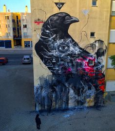 Constantly traveling around the globe, L7M is now in Europe where he just finished a series of new pieces in lovely Portugal. Painting on the streets of Loures, the Brazilian street artist dusted off one of his vibrant and colorful birds with this black crow which is entwined in colors and patterns. Roughness and elegance are