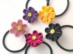 冬の差し色にもぴったりな、なごみカラーのヘアゴムをおつくりしました。  カラフルなまあるい梅のお花に、黄色の花芯がアクセント。  ほんのりくっきりの「なごみ色」で、ころんとかわいく。  お洋服にも合わせやすく仕上がりました。  ヘアゴムの直径は約5.5センチ。 個人差はありますが、女性の手首にフィットするくらいのサイズ感です。   【カラー】 ①スモーキーピンク:霧がかかったようなくすみのピンク。  ②ヤマブキ色:くっきり元気なイエロー。  ③紫:紫苑色。ニュアンスの美しいくすみのパープル。  ④ダークピンク:ローズがかった明るい牡丹色。  ⑤黒:艶感のあるブラック。   「つまみ細工」は、小さな正方形の生地を職人がピンセットを使って一枚一枚ていねいに折りたたみ、糊付けしてつくる、日本の伝統工芸です。  京都では、舞妓さんのかんざしにも使われています。  成人式や卒業式、入学式のお着物に合わせて。 結婚式やお呼ばれのドレスに。 特別な日のギフトに。  繊細な手仕事の一品をお手元にどうぞ。   寸法:お花の直径約3.5㎝/ヘアゴム直径約5.5㎝   同じ色の複数購入も可能です。…