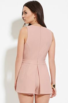 This midweight woven romper features a sleeveless cut, a plunging V-neckline, a slit at its layered front, and a concealed back zipper.