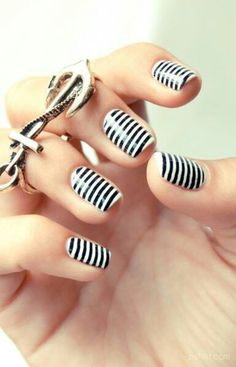 paint your nails white and let the completely dry. then cut out thin strips of tape and place them on your nails spacing them out equally. paint a coat of black polish on then remove tape while polish is still wet.