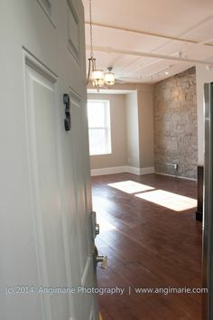 Unit #3 Entry. Restored maple flooring, granite wall, exposed pipes.