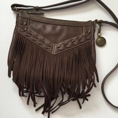 """Nine West Vintage America Crossbody Bag Nine West purse from the Vintage America Collection! Has fringe on the front. Adjustable Crossbody strap. Inside has one zipper pocket and two slip pockets for your keys, lip stick, etc. Has embroidered leather-like design on the front. Made of Quality Man Made Materials (that's what the tag says!). Strap has 22 1/2"""" drop, about 7"""" tall, about 9 1/2"""" wide, about 1 1/2"""" thick (without contents inside). Fringe about 4 1/2"""" past the bottom of bag. Great…"""