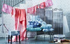 Ein Arrangement verschiedener Stoffe mit Shibori-Mustern gefärbt, u. a. Tischdecken, Servietten, Kissen, Hockerbezüge und Raumteiler in Rosa, Grün, Blau.