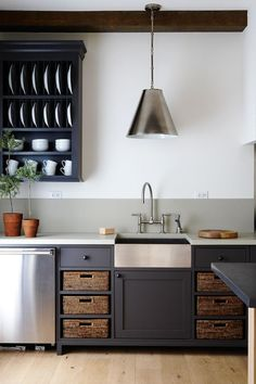 Fabulous!    The stunning, unfitted kitchen includes traditional country elements like an apron sink and open storage, mixed with modern charcoal grey cabinets, stainless steel accents and honed CaesarStone countertops.              Source: House & Home April 2010 issue  Products: CaesarStone counter, Ciot; cabinets, Michael Black; dishwasher, Sub-Zero; pendant light and sink, Elte;...