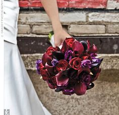 Eggplant-colored calla lilies, black Baccara roses and purple lisianthus dark, dramatic bouquet.
