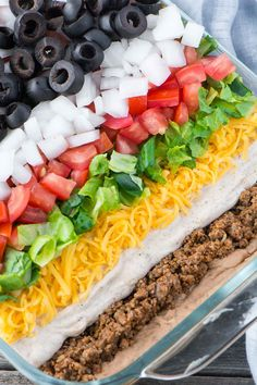 Mexican 7 Layer Taco Dip has seasoned beef, refried beans, three types of cheeses, and is garnished with your favorite toppings.