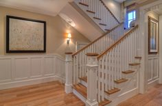 Finish carpentry transforms this stairway into a work of art.  Variegated hard wood flooring is accented by white wood pillars and stair rails.  www.detailsadesignfirm.com