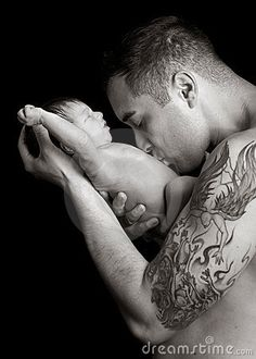 Newborn getting belly kisses from his daddy.  Father is holding the baby boy in his arms and kissing this tummy.  Feel the love in this beautiful black and white portrait.  Strength/protection of the father vs the soft innocence of the baby.