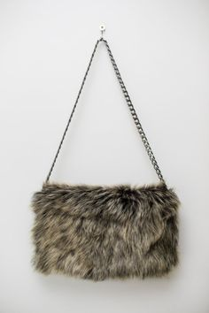 Goat fur clutch bag in dark olive colour unfolds to reveal two zip pockets and leather lining. Its very nice bag for going out . A delightful shoulder bag possible to wear like a clutch.. Dark silver tone chain shoulder strap. Colour-olive green Measures : ( folded out ) Length 32 cm 12,5