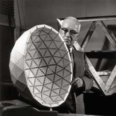 Bucky Fuller holding model of the Ford Rotunda dome designed by engineer T.C. Howard. Piece of the truss in background.