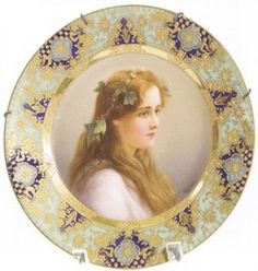 A Royal Vienna plate, signed Wagner, titled Hophen, depicting a young woman in a gossamer dress and ivy in her hair, border with scrolling over blue and green, beehive mark.