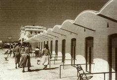 Años 60, Las desaparecidas casetas con su techo en forma de ola. Al fondo, el restaurante y el Hotel Playa..