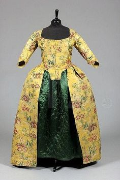A brocaded silk robe à l'Anglaise, the silk probably Spitalfields, 1730s, the construction 1770s, of brilliant yellow figurative silk brocaded with trees in a landscape and outsized blooms, closed front bodice; together with a green quilted satin petticoat