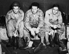 Three soldiers of Company G., 7th Infantry Regiment, 3rd Division, swap their combat boots for the new 'Mickey Mouse' thermal boots at their installation 'somewhere in Korea' Nov. 22, 1952. The new thermal boots are an improvement over shoe-pacs issued last winter to troops in the Korean fighting. From left are: Pfc. Claude J. Williams, Kansas City, Mo.; M/Sgt. Charles E. Hawkins, of Havre de Grace, Md.; and Cpl. James E. Hobbs, of Rushtown, Ohio. (AP Photo)