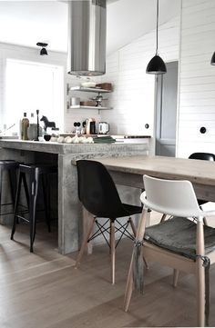 kitchen, pendant light, wood floor, concrete kitchen island, white walls