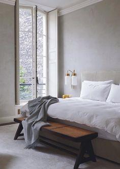 Colori chiari e splendide luci vintage a fianco al letto.