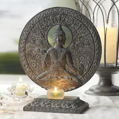"SERENE BUDDHA TEALIGHT HOLDER  Item #:  P99011Set the stage for peace and relaxation. Our Buddha Holder was specially designed with Buddhist virtues in mind – every detail has a meaning. Hand-painted resin has the look of sculptural stone. Frosted glass cup for use with tealights, sold separately. 12"" (30 cm) h, 10 1/4"" (26 cm) w, 5 1/4"" (13 cm) depth."