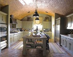 """""""Nothing scares this client except white,"""" says designer   Cathy Kincaid, """"so of course she didn't want the typical white kitchen."""" The Busby Gilbert Arabesque tiles on the backsplash and the Antique Terra Cotta Dark tiles on the floor are from Ann Sacks. Featured in the May 2009 issue."""