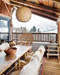 Cozy covered chic chalet winter porch with long wood farm dining table, sheepskin covered chairs, a wicker peacock chair at the head of the table, and woven wicker pendant lamp hanging from the eaves.