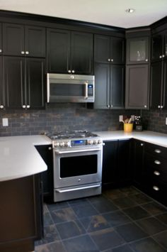 Classic black kitchen;  Thomasville cabinets, black on oak, white solid surface countertop, slate floor and backsplash.  U-shaped kitchen with a dramatic edge.