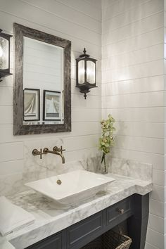 Benjamin Moore Maritime White lined with a pair of carriage house lantern sconces on either side of a rustic wooden vanity mirror
