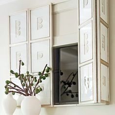 A series of framed white intaglios, mounted via piano hinges, cleverly hides the television- Southern Living