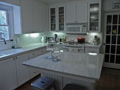 Carrara marble looks beautiful with white cabinets and appliances.
