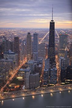 ohn Hancock Center rises above the surrounding buildings and Lake Shore Drive, aerial view during sunset.