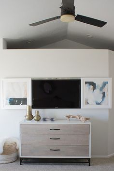 Hang a drawer slide above your TV to easily hide it behind pretty pieces of art.