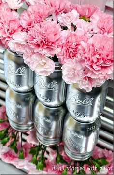 Glossy silver painted mason jars on a mirror, for a centrepiece