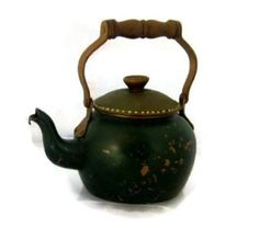 Small old copper kettle,painted green.Cover has golden dots.  Wooden handle,brown.  Painting was not done by me,so there is no knowledge