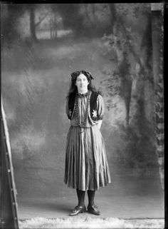 Studio portrait of an unidentified young woman in [costume?], with a frilly neck blouse and pleated skirt, star sequined vest and bead necklace, hair bows and buckled shoes, Christchurch