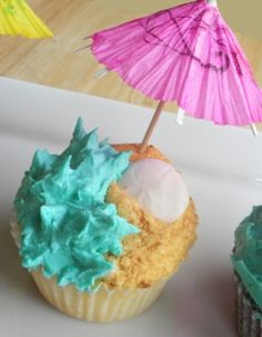 Cute cupcake design looks like the edge of the sea with a sand dollar and waves crashing and little beach umbrella.
