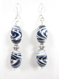 These handmade polymer clay tear drop earrings feature a gradient of blue, purple and white polymer clay accented with black and white stripes. Each earring features two oval polymer clay beads separated by a round antiqued silver corrugated metal bead that is attached to a flat silver plated earring hook. The oval polymer clay beads are coated in water based glossy varnish for high shine.  https://www.etsy.com/listing/150444704/polymer-clay-earrings-blue-purple-white?ref=v1_other_2