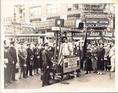 """Die Heilsarmee auf dem Times Square in New York in den 1930er Jahren mit einem für damalige Verhältnisse fortschrittlichen, zur Bühne mit Lautsprechern umfunktioniertem Anhänger. Das Gefährt wurde """"The Glory Shop"""" (der Herrlichkeits-Laden) genannt."""