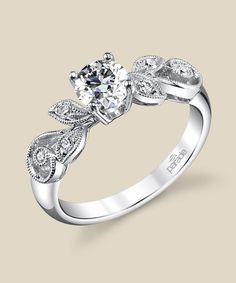 Meandering milgrain etched vines and diamond set leaves play up to a brilliant cut diamond center. Diamond Info: 06-RD 0.10 CTS Fits center stone size RD: 4.5-5.0 MM GUIDE Center stone not included.