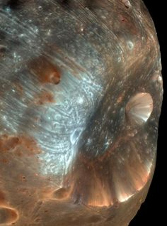 [astrogeology] A dramatic view of Phobos, one of the Mars' moons, and its largest crater Sticky, acquired by HiRES in March 2008. Fun fact: Phobos is closer to its planet than any other known moon, so close in fact that it orbits Mars faster than it rotates! Phobos' orbit lowers by one meter every century. Eventually it will collide with its planet or break up into a planetary ring. ~Al. A.
