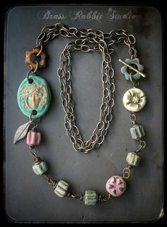 I love the rustic elegance of this necklace. The ceramic cameo focal was made by Nancey Snores and its got to be one of my favorite ceramic focals of all time I love the soft earthy tones and subtle details. There are also ceramic beads by Marsha Neil, Start Road Studio, and a beautiful clay double sided flower lentil by Heather Powers and a bronze leaf charm by The a Elements. The beads and connectors are all wire wrapped with Vintage 20 gauge brass wire and