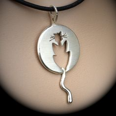 sterling silver Cat Pendant by AngelaWrightDesigns. The cat silhouette was cut out using a jeweler's bench saw. The piece has a satin finish and burnished edges to catch the light beautifully. The back is brushed and stamped with the makers mark, which is registered with the Sheffield Assay Office. The pendant measures 2.8 cm in diameter 5cm long.