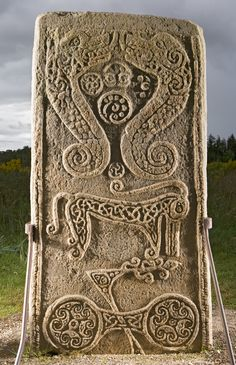 It is sculptured in relief, with Ogham inscriptions down each of the four angles. The front bears a celtic cross with interlacing, and the back bears symbols including fish monsters, the elephant or dolphin, double disc and z-rod.