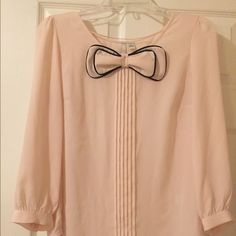 LC Lauren Conrad blouse Light pink/cream blouse with bow detail. Pleating down front with cuffed sleeves LC Lauren Conrad Tops Blouses