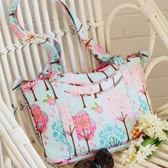 Styled shot of pastel handbag with pockets on chair with flowers