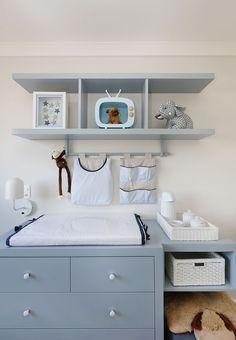 Decoração de apartamento integrado e com crianças. No quarto infantil, quarto de menino, detalhes azuis, prateleiras azuis, cômoda azul, trocador e adornos.