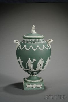 Wedgwood Green Jasper Dip Vase and Cover, England, early 20th century, applied white relief with a cherub finial, Medusa mask and snake handles and figures of classical Muses beneath floral festoons, various foliate borders.